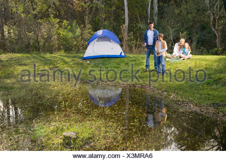 Family having fun on camping trip fishing by tent - Stock Photo