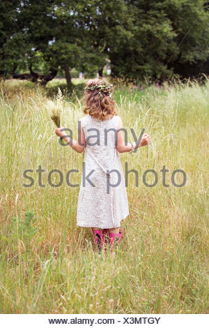 Young girl with flowers in her hair picking wild flowers in a meadow. - Stock Photo