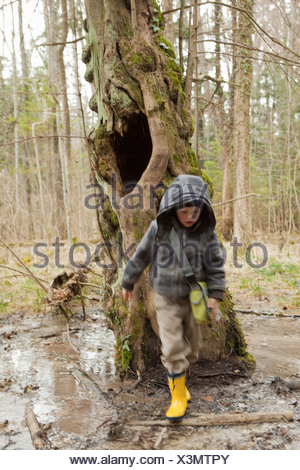 Boy sloshing through mud in a forest - Stock Photo