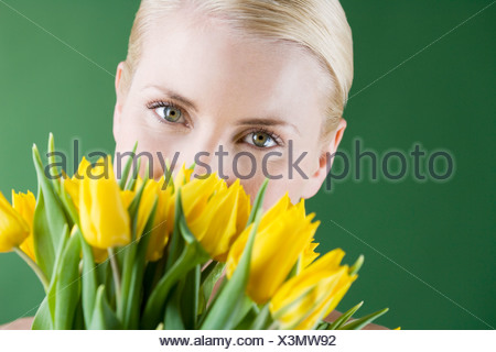 A young blonde woman holding a bunch of yellow tulips - Stock Photo
