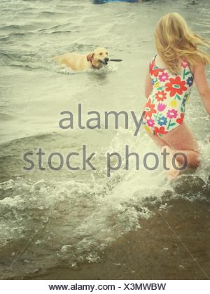 Girl In Swimming Costume Playing With Dog At Beach - Stock Photo