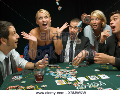 Happy woman throwing poker chips at poker game - Stock Photo
