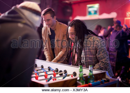 Group of men playing table football in bar - Stock Photo