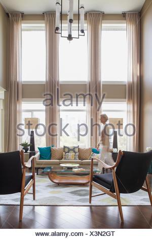 Woman walking in modern living room - Stock Photo