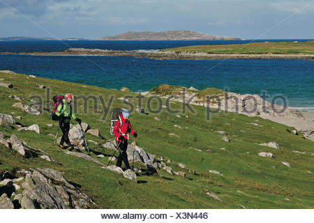 Hikers passing beach between Huisinis and Loch Crabhadail, Harris, Lewis and Harris, Outer Hebrides, Scotland, Great Britain - Stock Photo