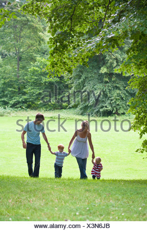 Mid adult couple with children walking in park - Stock Photo