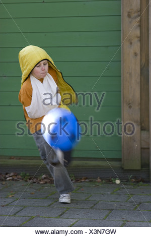 Rude young boy showing disrespect, kicking soccer ball, almost knocks me out. - Stock Photo