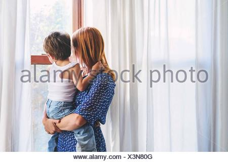 Mother and boy (2-3) child looking out of window - Stock Photo