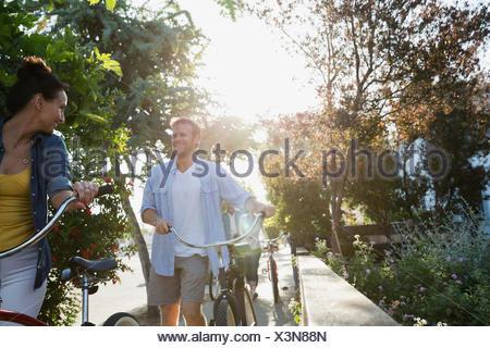 Couple riding bicycles on sunny sidewalk - Stock Photo