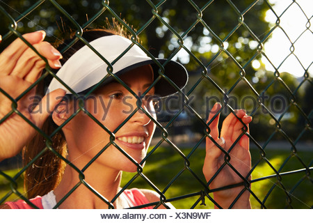 Woman peering through chain link fence - Stock Photo