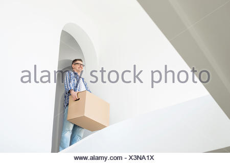 Man carrying cardboard box in new home - Stock Photo