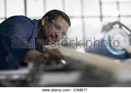 Carpenter checking straightness of plank in workshop - Stock Photo
