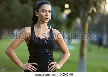 Mid adult woman wearing earphones, hands on hips - Stock Photo