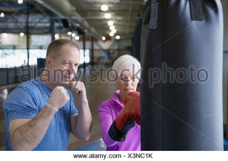 Woman boxing with personal trainer at gym - Stock Photo