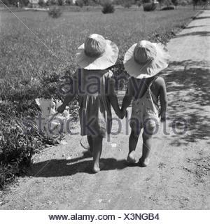 Zwei kleine Kinder bei einem Spaziergang in der Sonne, Deutschland 1930er Jahre. Two toddlers strolling through summer, Germany 1930s. - Stock Photo