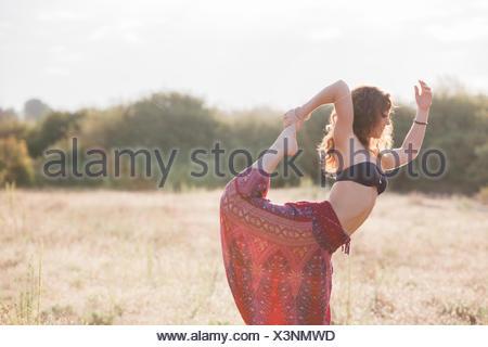 Boho woman in king dancer yoga pose in sunny rural field - Stock Photo