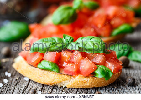 Tomato bruschetta with chopped tomatoes and basil on toasted bread - Stock Photo