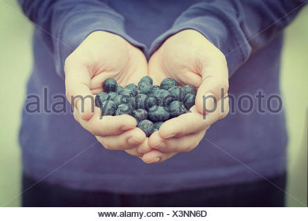 Close-up of Man holding a handful of blueberries - Stock Photo