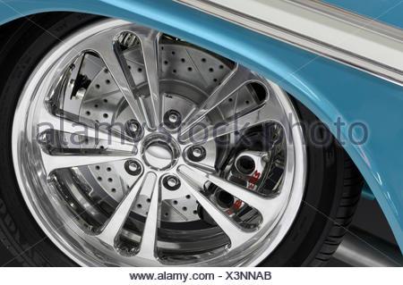 Shiny chrome plated custom car rim on a low profile tire closeup