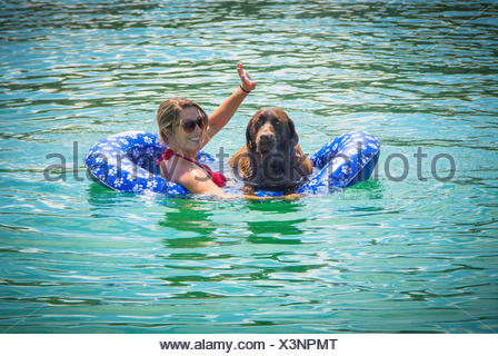 Woman and chocolate labrador retriever dog in ocean on floatation device - Stock Photo