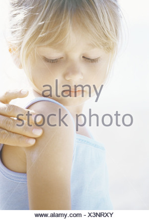 Girl having sunscreen applied to shoulder - Stock Photo