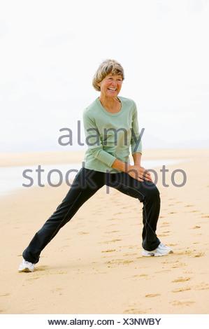 full body portrait of mature woman exercising on beach - Stock Photo