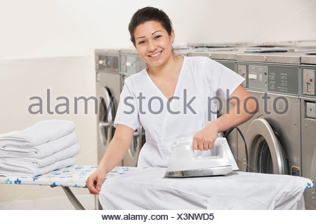 Portrait of a happy young woman ironing clothes in Laundromat - Stock Photo