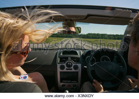 Couple in car driving along country road - Stock Photo