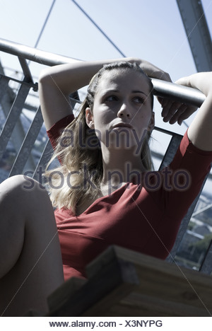 young woman in red sitting on a bench with her arms over a railing - Stock Photo