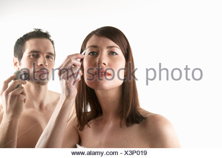 Young woman plucking her eyebrows with man shaving in background - Stock Photo