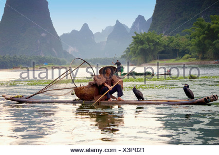 Fisherman fishing in a river with a hill range in the background, Guilin Hills, XingPing, Yangshuo, Guangxi Province, China - Stock Photo