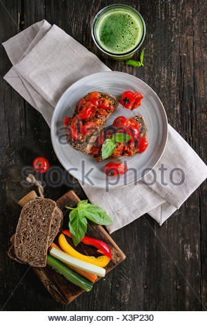 Italian tomato bruschetta with baked cherry tomatoes and sliced vegetables, served on gray ceramic plate with textile napkin and - Stock Photo