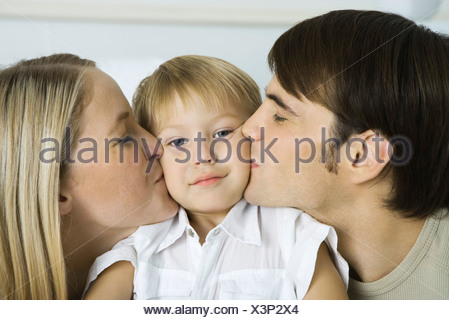 Parents kissing little boy's cheeks, boy looking at camera - Stock Photo
