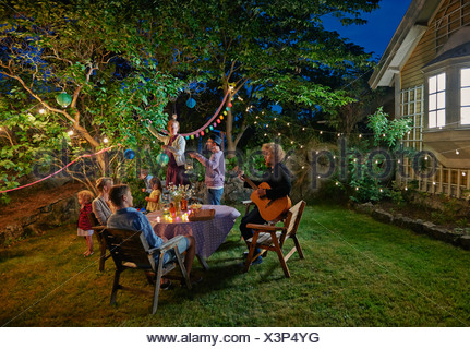 Family group preparing for evening garden party - Stock Photo