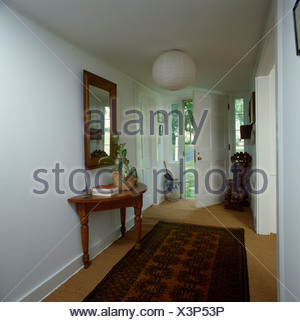 oriental rug on carpet. Oriental Rug On Sisal Carpet In Traditional White Hall With Mirror Above Antique Console Table - R