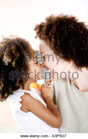 Happy mother and daughter touching noses - Stock Photo