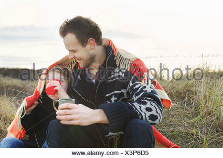 Smiling mid adult man and son wrapped in blanket on sand dunes - Stock Photo