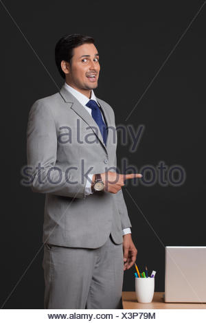 Portrait of young businessman pointing sideways in office - Stock Photo