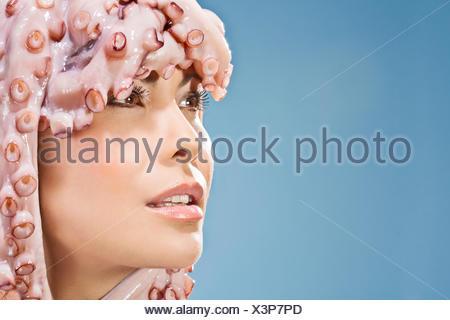 Portrait of woman wearing octopus headdress - Stock Photo