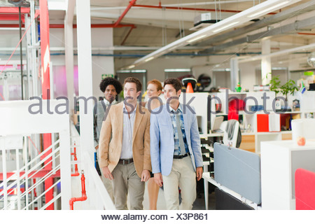 Businessmen walking together in office - Stock Photo
