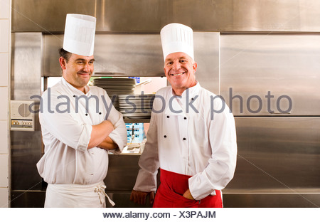 Two male chefs standing in commercial kitchen smiling portrait - Stock Photo