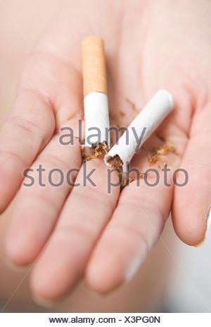 Hand holding a cigarette broken in half - Stock Photo