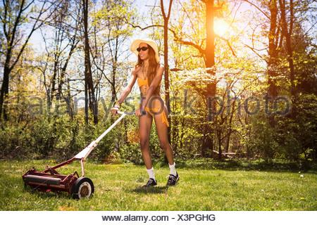Woman wearing bikini mowing grass - Stock Photo