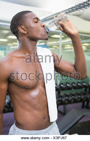Shirtless man drinking water at gym - Stock Photo