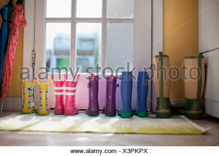 Tidy row of rubber boots at back door - Stock Photo