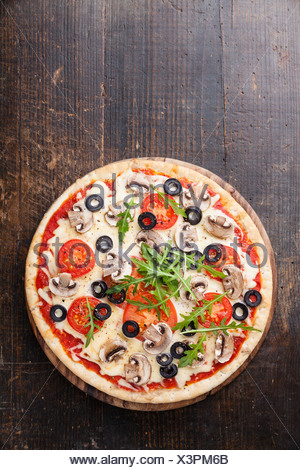 Pizza with mushrooms and ruccola on wooden table - Stock Photo