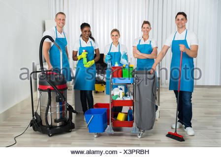 Cleaners With Cleaning Equipments In Office - Stock Photo
