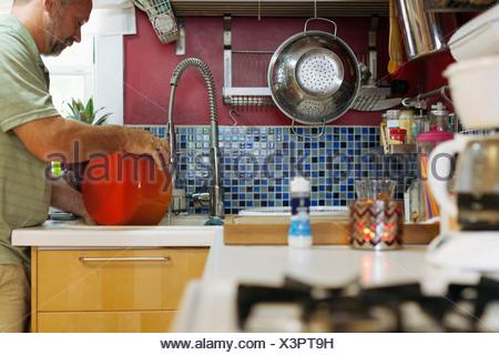 Man washing red pot - Stock Photo