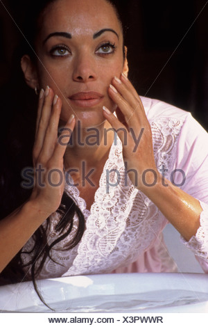 Beautiful woman of mixed ethnicity washers her face - Stock Photo