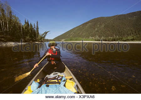 Adult male paddles canoe on *Wild River* Birch Creek in Steese National Conservation Area summer Interior Alaska - Stock Photo
